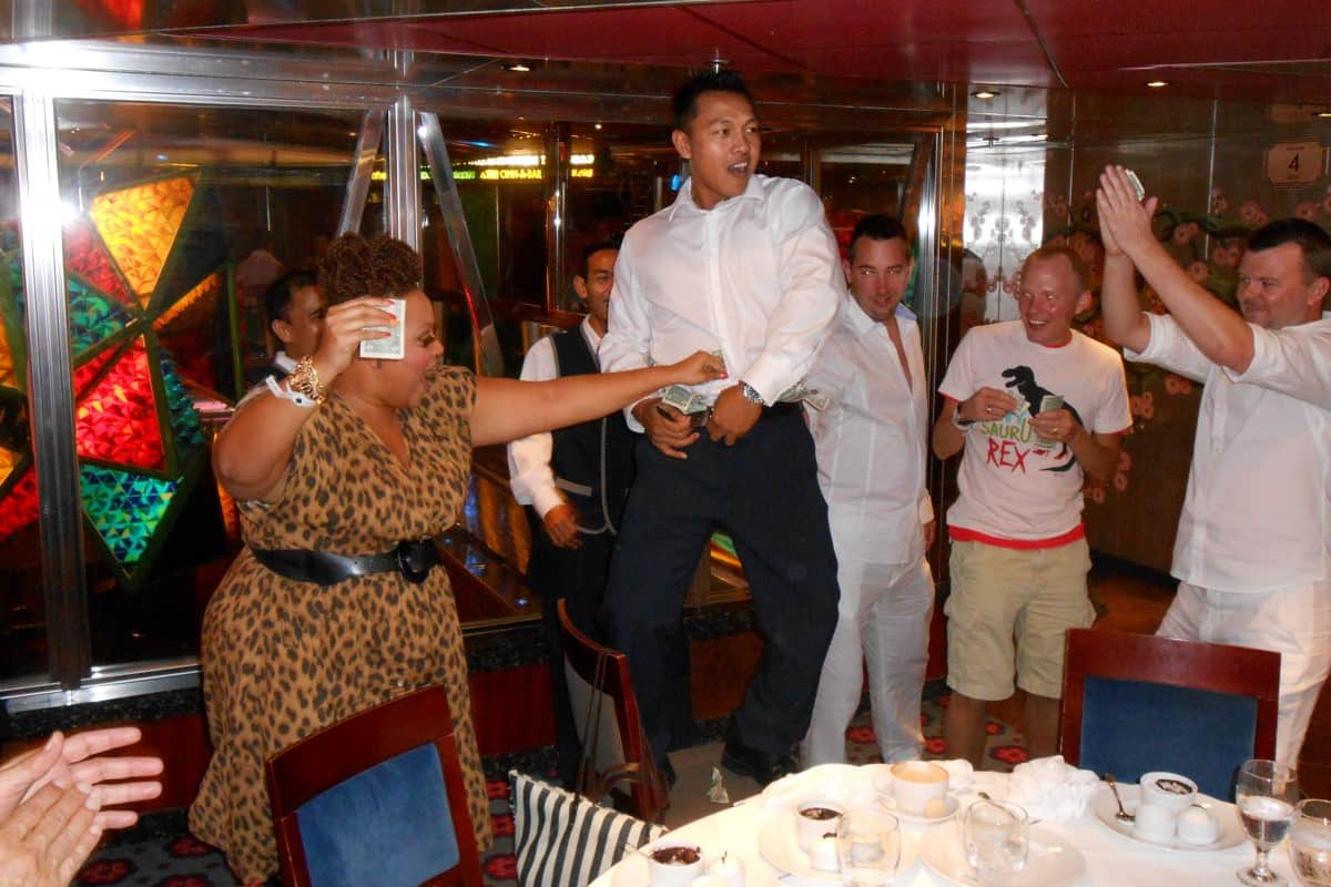 Konobar igra na stolu dok mu vesela putnica daje pare.