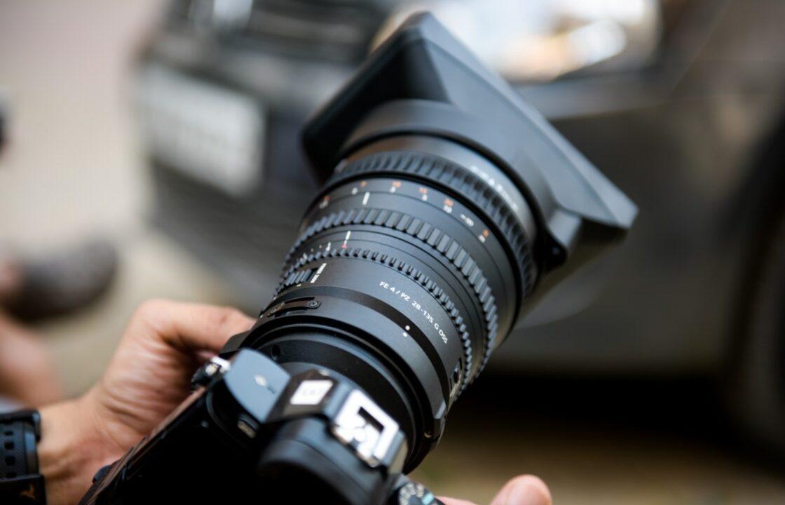 Fotograf drzi profesionalni fotoaparat u ruci.