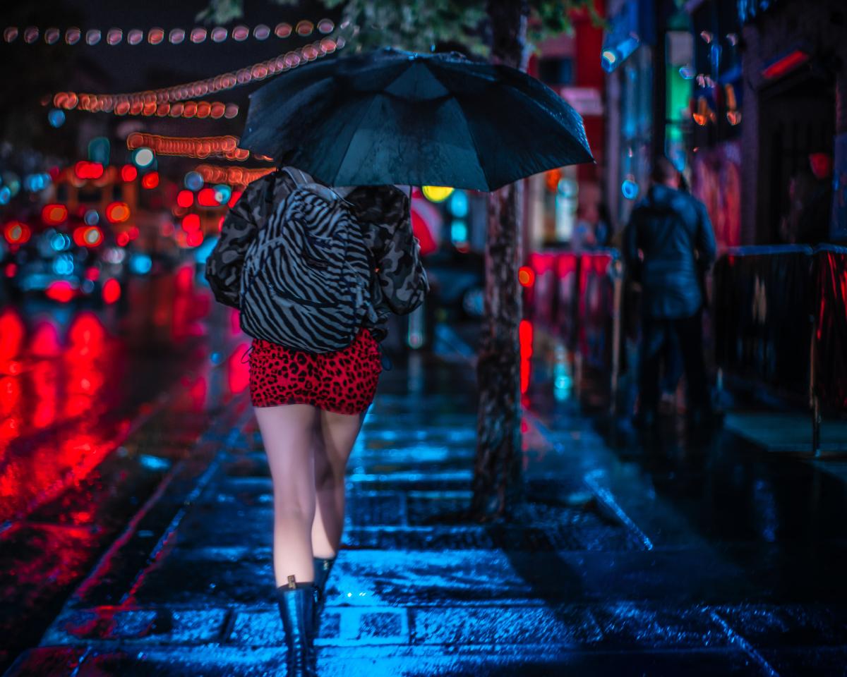 Devojka u crvenoj mini suknji sa kisobranom hoda ulicom.