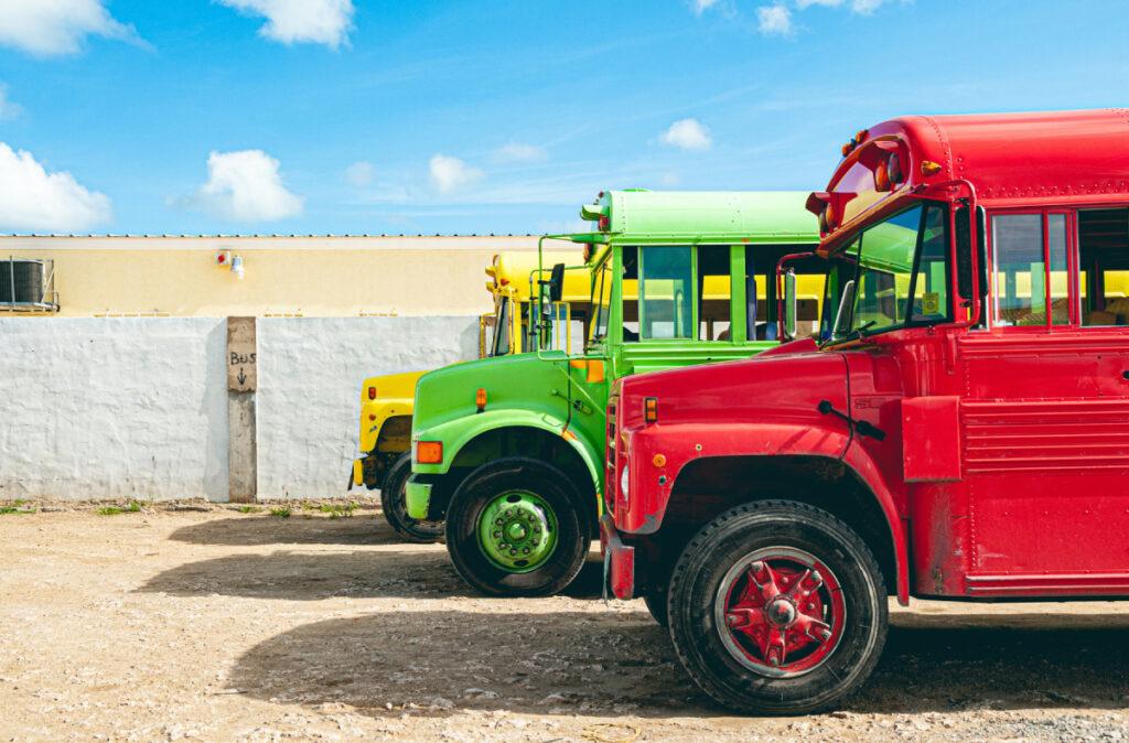 Crveni, zeleni, zuti kamion stoje na parkingu.